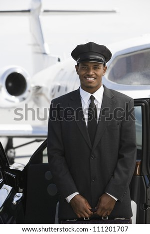 Portrait of a car driver standing by car with airplane in the background at airfield - stock photo