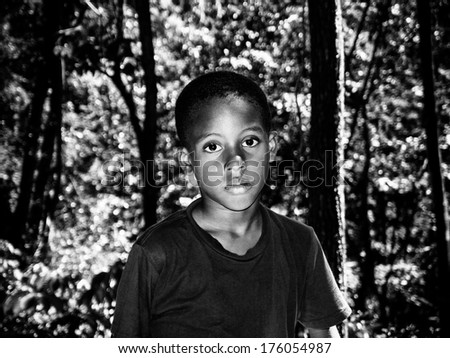 portrait of a caribbean boy in the woods - stock photo