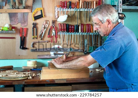 portrait of a carpenter planing on a piece of wood at work in the workshop - stock photo