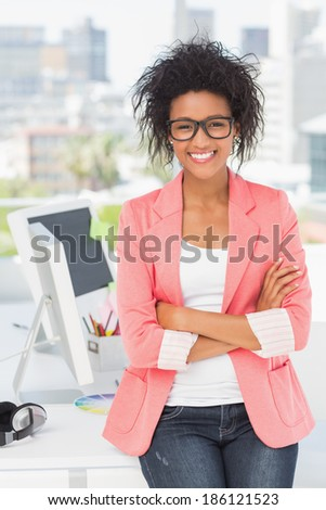 Portrait of a casual female artist standing with arms crossed at a bright office - stock photo