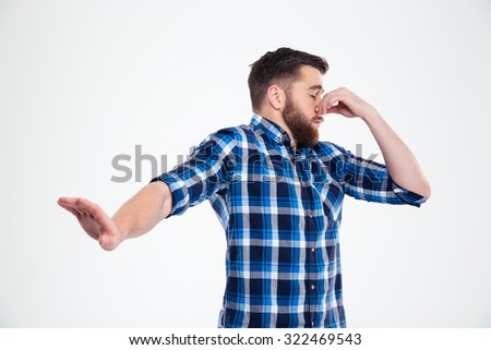 Portrait of a casual man covering his nose and showing stop gesture with palm isolated on a white background - stock photo