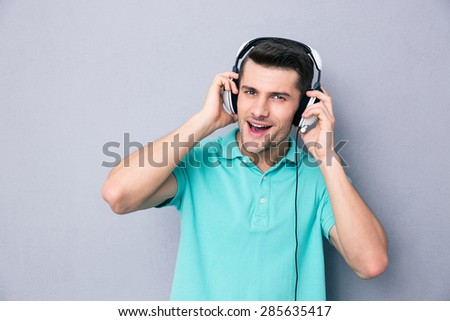Portrait of a casual man in headphones over gray background - stock photo