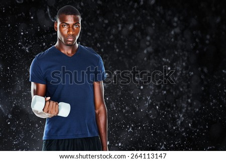 Portrait of a casual man lifting dumbbells against black background - stock photo