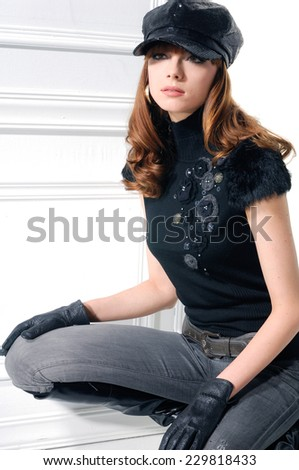portrait of a casual young fashion model in cap posing  - stock photo
