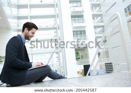 Portrait of a casual young man working on laptop - stock photo