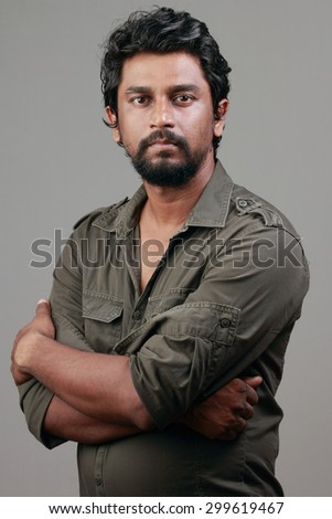 Portrait of a casually dressed Indian young man with beard - stock photo
