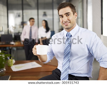 portrait of a caucasian business executive holding a cup of coffee in office with colleagues in the background. - stock photo
