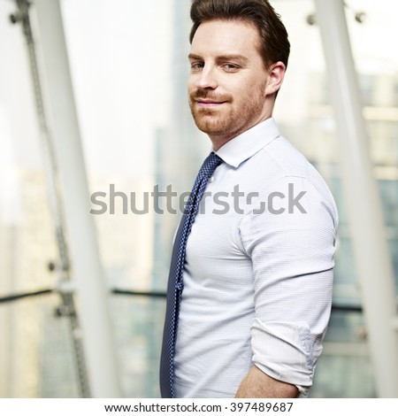 portrait of a caucasian business executive standing by the window in office, hands in pockets, side view. - stock photo