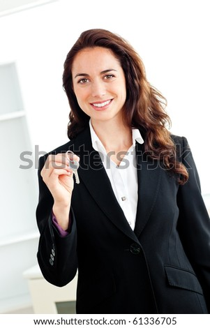 Portrait of a caucasian businesswoman holding a key against a white background - stock photo
