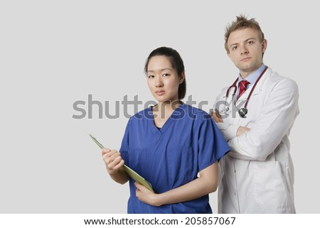 Portrait of a Caucasian doctor standing with an Asian nurse over gray background - stock photo