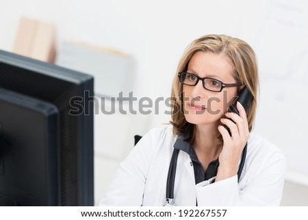 Portrait of a Caucasian middle-aged female physician, with eyeglasses, stethoscope and white medical coat, holding the mobile phone to the ear while reading useful information from a large monitor - stock photo