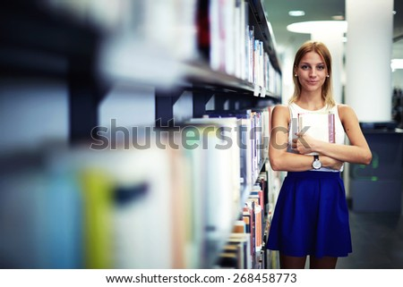 Portrait of a caucasian smiling female student holding book while standing in university library, pretty young woman standing near bookshelves in bookstore shop, exam preparation in university - stock photo