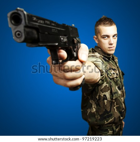 portrait of a caucasian soldier with a jungle camouflage pointing with a pistol over a blue background - stock photo