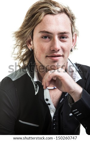 portrait of a caucasian young man with long grungy bond hair dressed in a black and white dress shirt resting his chin on his hand seductively - stock photo