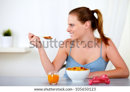 Portrait of a caucasian young woman smiling and eating healthy meal at home indoor - stock photo