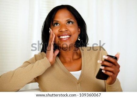 Portrait of a charming black woman holding a mobile phone while is looking up - stock photo