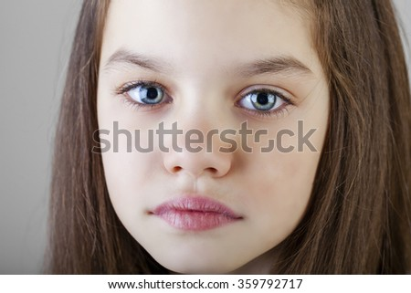Portrait of a charming brunette little girl, isolated on gray background - stock photo