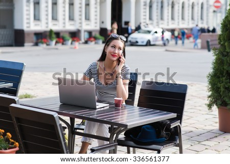 Portrait of a charming brunette woman having mobile phone conversation during work on laptop computer, gorgeous female calling with cell telephone while sitting with portable net-book in sidewalk cafe - stock photo