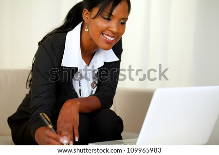 Portrait of a charming businesswoman on black suit working while sitting on couch in front of her laptop - stock photo