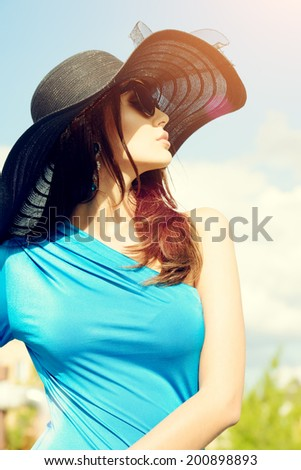 Portrait of a charming lady in beautiful elegant dress and hat against the sky. - stock photo