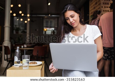 Portrait of a charming latin woman having video conference on her net-book during lunch break in modern coffee shop,young female designer using laptop computer for distance work while sitting in cafe  - stock photo