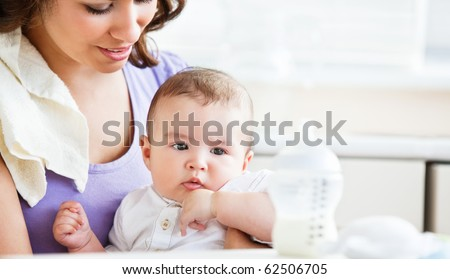 Portrait of a charming mother taking care of her adorable baby in the kitchen at home - stock photo