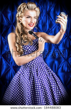 Portrait of a charming pin-up girl painting lips with red lipstick. - stock photo