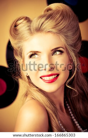 Portrait of a charming pin-up woman with retro hairstyle and make-up posing with vinyl record. - stock photo