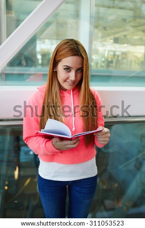 Portrait of a charming smiling teenager girl with long beautiful hair holding notepad while standing in the hallway of college campus,attractive student reading workbook or notebook in school interior - stock photo