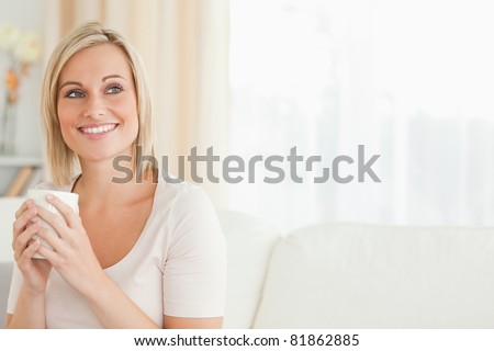 Portrait of a charming woman holding a cup of tea looking away from the camera - stock photo