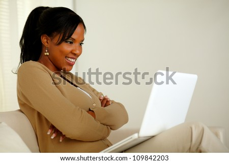 Portrait of a charming woman looking to laptop screen while sitting on sofa at home indoor - stock photo