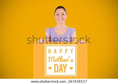 Portrait of a charming woman posing behind a billboard while standing against yellow background with vignette - stock photo