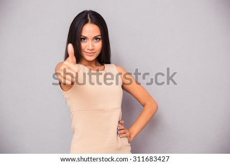 Portrait of a charming woman showing thumb up over gray background - stock photo