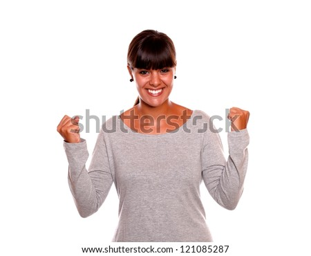Portrait of a charming young female celebrating a victory while is looking at you standing on isolated background - stock photo