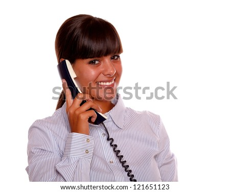 Portrait of a charming young female conversing on phone while is looking at you on isolated background - stock photo