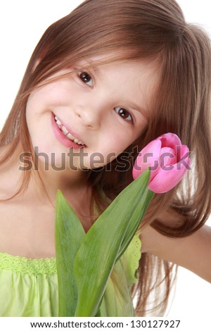 Portrait of a charming young girl with beautiful hair/Beautiful little girl with long hair holding a pink tulip - stock photo