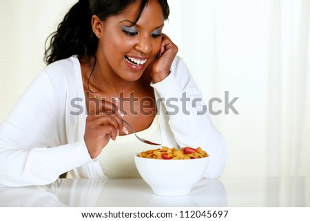 Portrait of a charming young woman eating a bowl of cereals with strawberries at soft colors composition. with copyspace - stock photo
