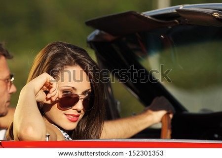 Portrait of a charming young woman in a convertible car - stock photo