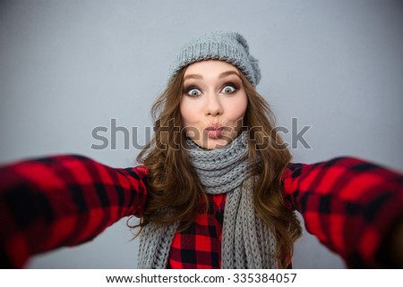 Portrait of a charming young woman making selfie photo over gray background - stock photo
