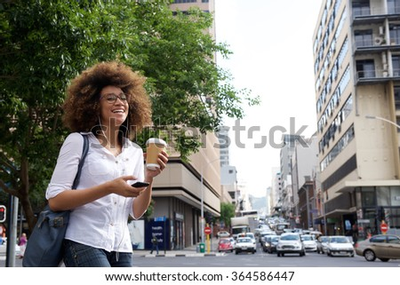 Portrait of a cheerful african american woman walking in the city with cell phone - stock photo