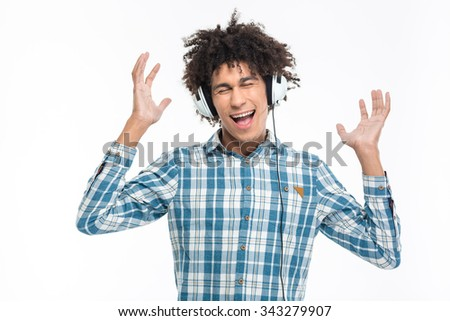 Portrait of a cheerful afro american man listening music in headphones isolated on a white background - stock photo