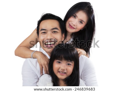 Portrait of a cheerful asian family smiling at the camera in the studio, isolated on white background - stock photo