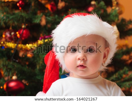Portrait of a cheerful baby girl with Santa hat - stock photo