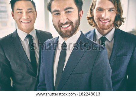 Portrait of a cheerful beaded businessman posing with his colleagues on the foreground  - stock photo
