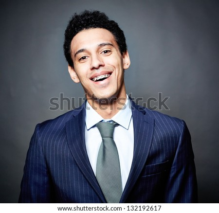 Portrait of a cheerful business guy with braces, against black background - stock photo