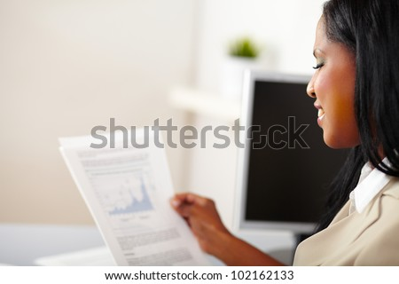 Portrait of a cheerful business woman reading documents - stock photo