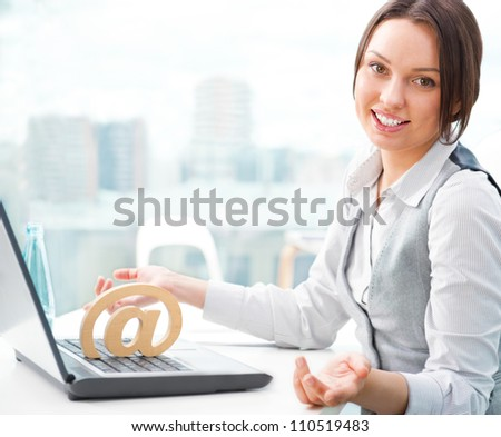 Portrait of a cheerful Business woman sitting on her desk and smiling. At symbol on her laptop - stock photo