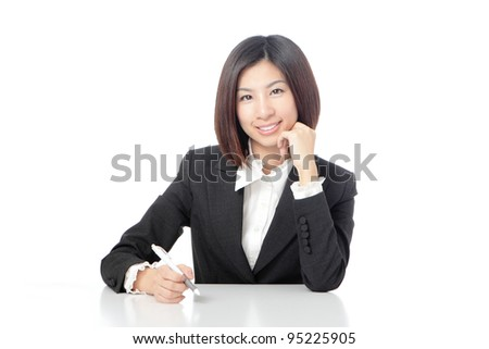 Portrait of a cheerful Business woman sitting on her desk holding a pen isolated over white background, model is a asian beauty - stock photo