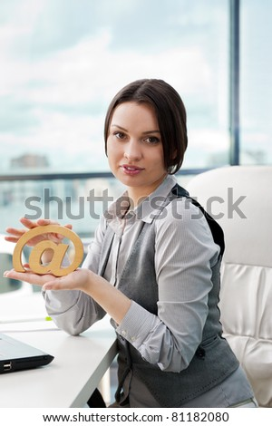 Portrait of a cheerful Business woman sitting on her desk holding an at symbol - stock photo