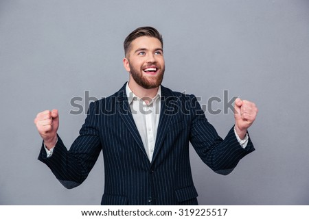 Portrait of a cheerful businessman celebrating his success over gray background - stock photo